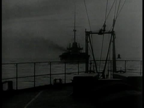 British battle fleet at sea MS Battleship at sea deck FG CU Cannon barrels ships BG WS Destroyer ships CU Cannon turning World War I WWI