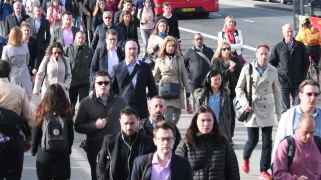 British business people on morning commute walking to work across London Bridge