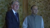 British finance minister Philip Hammond exchanges a handshake with his Indian counterpart Arun Jaitley on the first day of his visit in India in an...