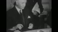 British Foreign Secretary Anthony Eden signs declaration Soviet Minister Vyacheslav Molotov looks on and blots ink on previous signature / United...