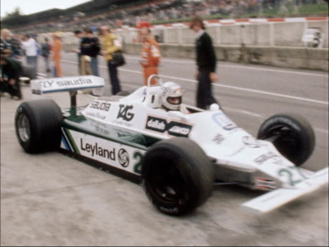 British Grand Prix ENGLAND Kent Brands Hatch EXT Alan Jones in Car 27 Saudia Leyland Williams in pits Jones car along from pits Cars along in...