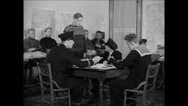MS British guard by poster 'Warning be on your guard' / DRAMATIZATION INT VS British Intelligence Officers interviewing Norwegian refugee about their...