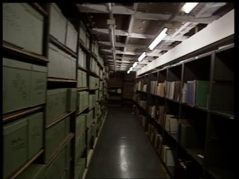 London British Library AV Metal balcony in corner TILT DOWN shelves of books FORWARD past shelves crammed with books MS TRACK SIDEWARDS RL past rows...