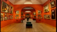 British Mona Lisa painting goes on display Reporter to camera as towards thru gallery