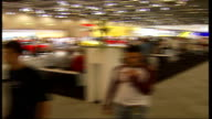 British Motor Show held at Excel Centre in London INT General View People wandering around at show PAN around 360 degrees Man gets into driving seat...
