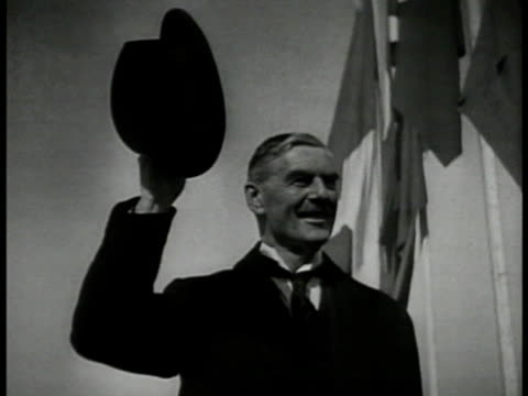 British Prime Minister Neville Chamberlain standing holding hat in air smiling WS PAN Crowd PACKED in city square w/ arms extending in Nazi salute LA...