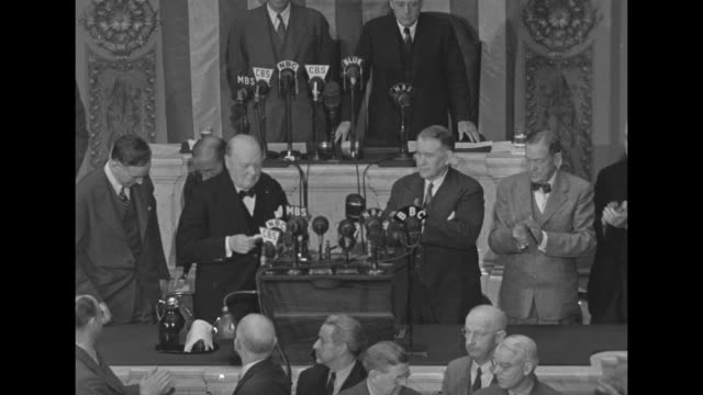 British Prime Minister Winston Churchill mounting rostrum in House of Representatives chamber with various members of US Congress / Churchill...