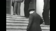 British Prime Minister Winston Churchill standing and waiting on steps up to porch he walks up steps and stands Soviet Premier Joseph Stalin standing...