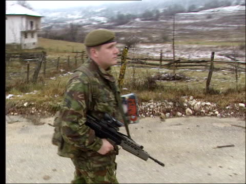 ROLE LIB EXT British soldiers on patrol along road
