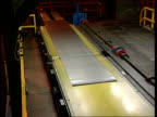 British Steel state aid challenge INT Llanwern OUT sheet metal along conveyor TMS Worker along TCMS Worker rubbing something by hand over sheet metal...