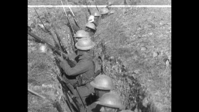 WWI British Tommies march on a dusty trail in a long line / slow pan down soldiers with rifles in a trench / men in a trench prepare rifles / Tommies...