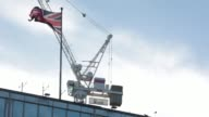A British Union flag flies from a pole near a construction crane stands in the sky above New Scotland Yard the headquarters of London's Metropolitan...