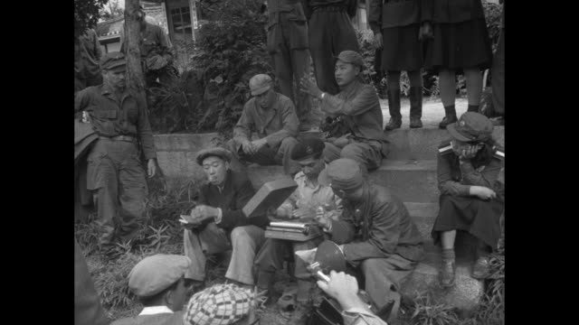 British war correspondent sits with typewriter on his lap probably a Korean translator beside him and South Korean men and women soldiers around him...