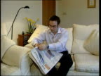 Briton Tim Selby taken hostage ITN Oldham Jon Selby reading newspaper as sitting on couch