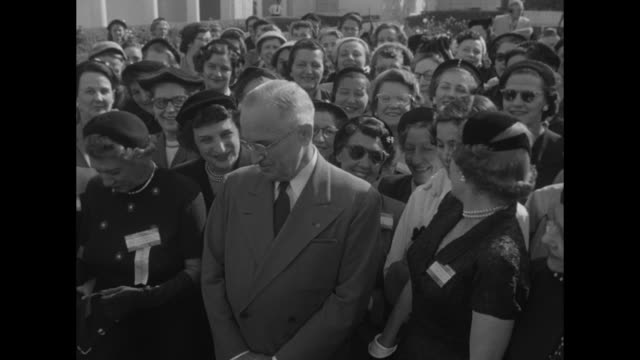 VS broadly smiling President Harry Truman standing with Theatre Owners of America members' wives in the White House Rose Garden