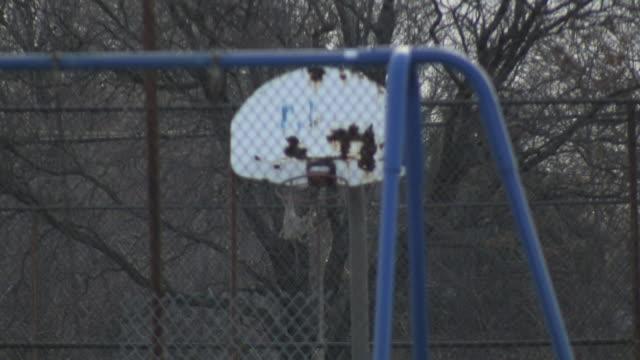 Broken bent rim of outdoor basketball hoop dilapidated backboard cross chain fence partial metal bar of swing set FG Poor slums streets ghetto poverty