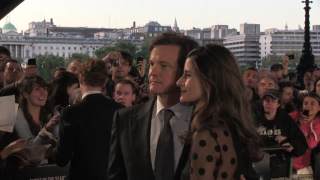 Gary Oldman clears the way for Colin Firth and Livia Giuggioli to pose for photographers at the UK Premiere of Tinker Tailor Soldier Spy BRoll Colin...