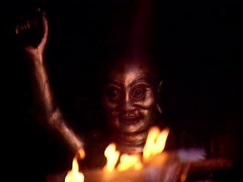Bronze statue with arm raised seen through flickering flames in temple Indonesia