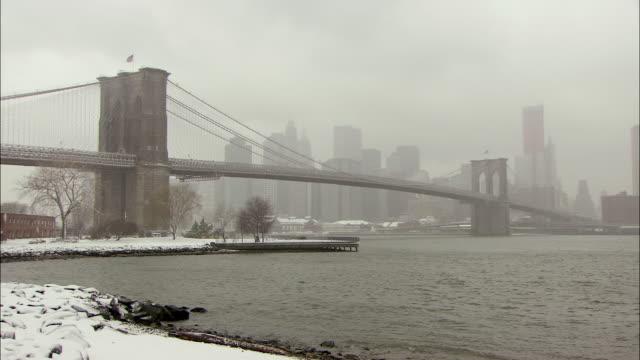 WS Brooklyn Bridge with Manhattan downtown skyline on snowy day / New York City, New York, USA