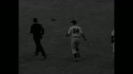 Brooklyn Dodgers' Pee Wee Reese gets hit in game 6 of World Series at Yankee Stadium / tiltdown LS baseball diamond with game in play two Dodgers...