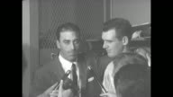 Brooklyn Dodgers pitcher Sal Maglie wearing a suit stands with New York Yankees pitcher Don Larsen in Yankees' locker room surrounded by journalists...