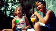 Brother and sister drinking juice