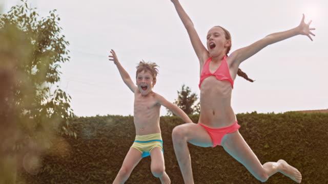 SLO-MO Schwester und Bruder springen in pool während dem Sonnenuntergang