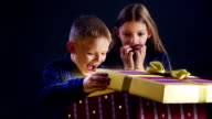 Brother and sister opening Christmas gift