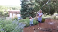 brother and sister playing with water hose