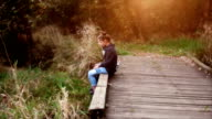 brother and sister sitting and talking on wooden bridge