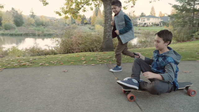 Brothers Playing with an Electric Skateboard
