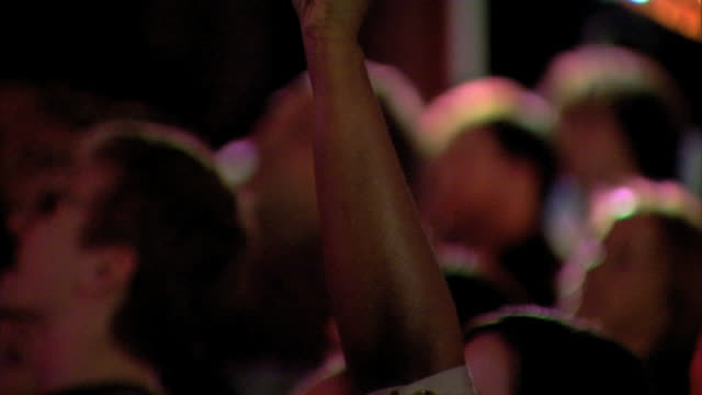 Brown skin arm TU IN FOCUS Arm Hand in fist raised above crowd w/ thumb nail painted w/ fingernail polish