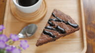 Brownie chocolate cake on wooden plate with coffee in cafe , dolly shot left to right