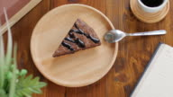 Brownie chocolate cake on wooden plate with coffee in cafe , dolly shot right to left