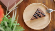 Brownie chocolate cake on wooden plate with coffee in cafe , dolly shot