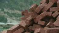 brownish-red bricks in a pile outside