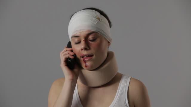 CU, TU, Bruised woman with bandaged head and neck brace on phone