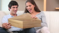 Brunette woman opening a gift with her boyfriend