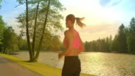 SLO MO Brunette woman running along a lake in sunshine