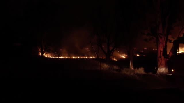 Brush fire threatens 300 homes near Prado Dam / Firetruck backing up / pan to brush fire