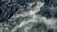 Bubbles and foam form in the wake of a ship. Available in HD.