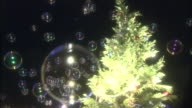 Bubbles float near a lighted Christmas tree.