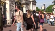 Police reveal suspect had a fourfoot sword Buckingham Palace Various of police outside palace gates Tourists along past gates Vox pops tourists...