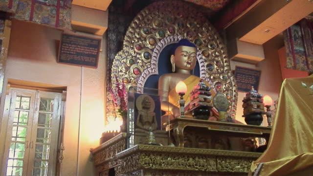 MS PAN Buddha statue and Tibetan scriptures in bookshelf, McLeod Ganj (Dharamsala), India