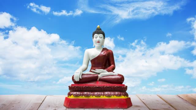 Buddha-statue auf Holz Etage mit Zeitraffer Wolken im Hintergrund verschieben