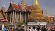 Buddhist architecture and tourists at Wat Phra Kaew in the Grand Palace complex in Bangkok, Thailand
