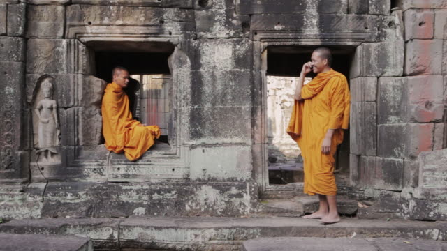 WS A Buddhist monk attempts to meditate while another talks and laughs on a mobile phone at an ancient temple in Angkor Wat / Siem Reap, Cambodia