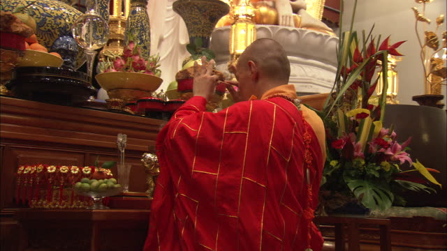 MS, Buddhist monk praying at altar in Siong Lim Temple, Toa Payoh, Singapore