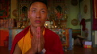 A Buddhist monk sits and prays. Available in HD.