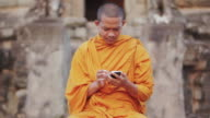 CU A Buddhist monk taps on the screen of a smartphone on an ancient temple in Angkor Wat / Siem Reap, Cambodia